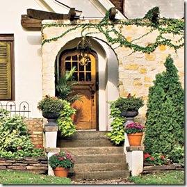 Porta de casa estilo cottage com vasos na escadaria