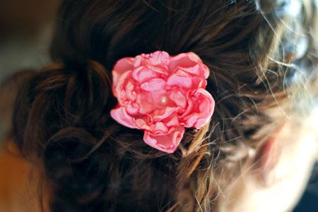 Flor de tecido queimada com vela num arranjo para cabelos
