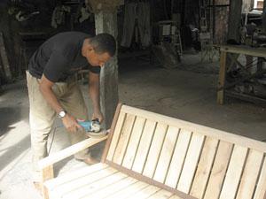 O Marcos trabalhando num de seus bancos de pallets