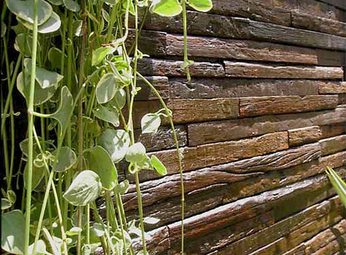 Revestimento de parede com madeira de demolição, em forma de tijolos estreitos, produto Pau Velho