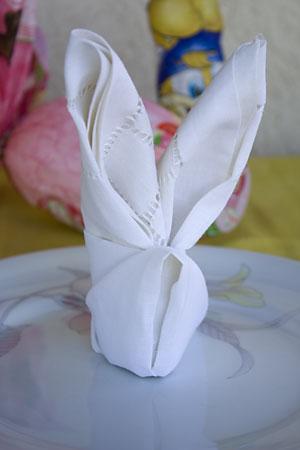 O guardanapo de coelho em cima do prato tá uma graça