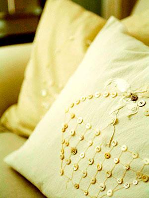 Almofada decorada com um motivo bordado em botões