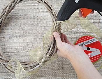 Fixe a fita decorativa em torno da guirlanda usando cola quente