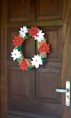 Guirlanda de flores de feltro enfeitando porta de entrada