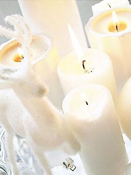 Mesas e aparadores cobertos de castiçais e velas brancas