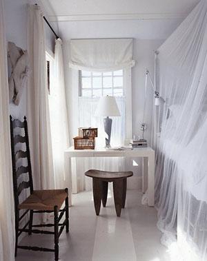 Quebrando o ambiente totalmente branco, o banquinho de madeira