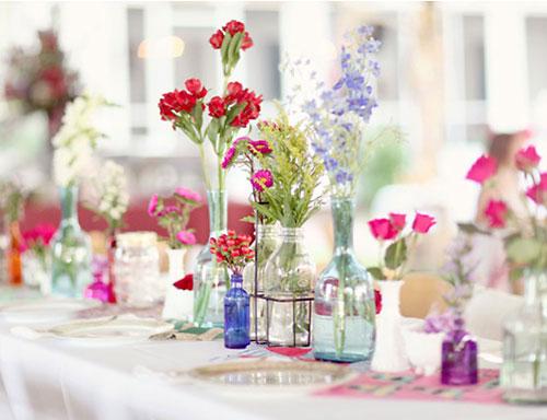 Vidros dispostos em linha no centro da mesa são um belo arranjo