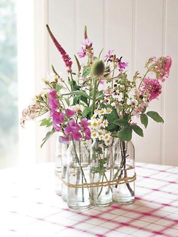 Garrafas de vidro usadas como vaso de flores