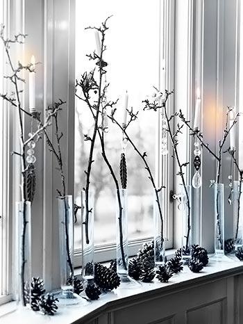 Galhos em vasos numa árvore descontruída e pinhas no aparador