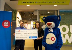 Jennifer Muench, BMO Vancouver Vice President with BMO the Bear, presented the $500,000 BMO Financial Group donation to Bryan Tisdall, CEO of Science World at the Our World BMO Sustainability Gallery