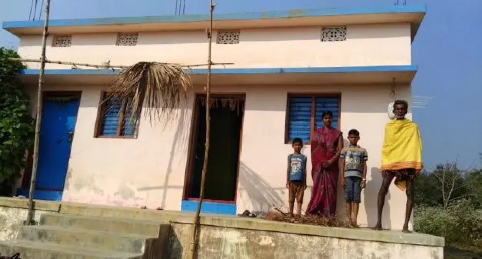 Damayanti Patra with her sons and father in front the house she built after Cyclone Phailin. (Photo by Gram Vikas)