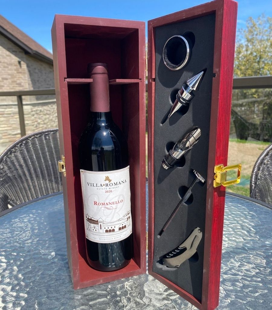 Wine box with bottle stoppers, wine collar, and a foldable corkscrew, with a bottle of red wine inside, sitting on a glass table outdoors.