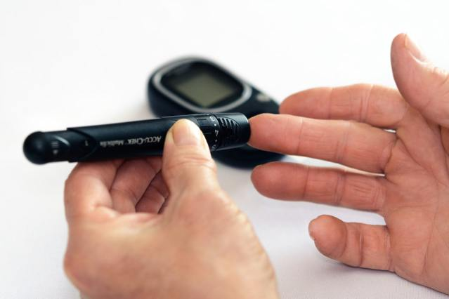A diabetic person using a blood glucose monitoring device.