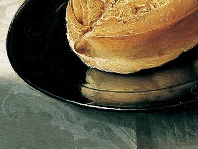 Détail de Nature morte avec fruits, noix et fromage. L'assiette métallique met en valeur le pain dont on voit le reflet. L'ombre de l'assiette et le changement de la lumière sur la nappe souligne sa position au bord de la table.