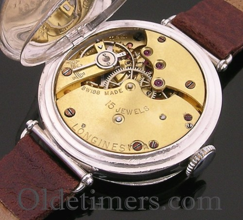 An early 9ct gold round vintage Longines watch. The case measures 33mm in diameter, with a hinged protective cover to the movement. The case is signed AB (Arthur Baume director of Longines UK) Swiss, hallmarked London 1915 and numbered. The movement is signed Longines, Swiss Made, with 15 jewels and having 'pin-set' hands. The white enamel dial has black open Arabic numerals with a subsidiary seconds dial and blued steel hands. The dial is signed Longines above the centre.