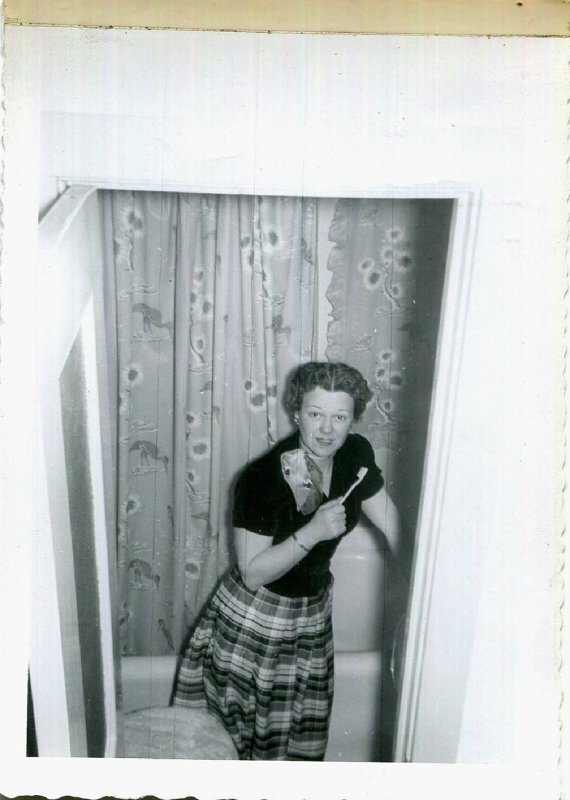 1950s woman in the bathroom brushing teeth vintage image