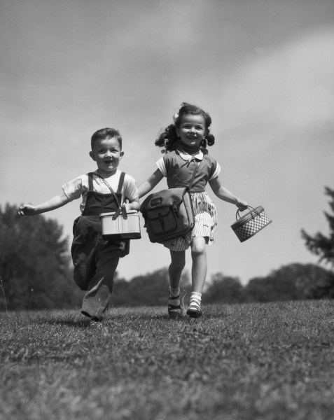 1950s two children running with lunchboxes