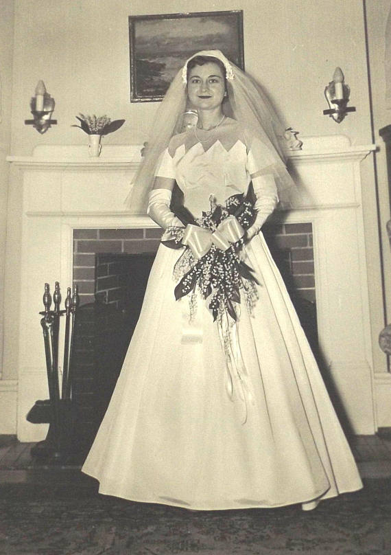 Vintage photo of a 1950s bride in her wedding dress with scalloped neckline