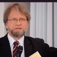 Antanas mockus dando un discurso con un micrófono y una hojas de papel