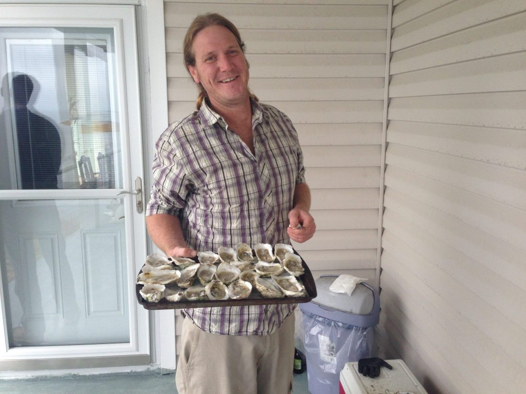 big island man holding oysters in tray