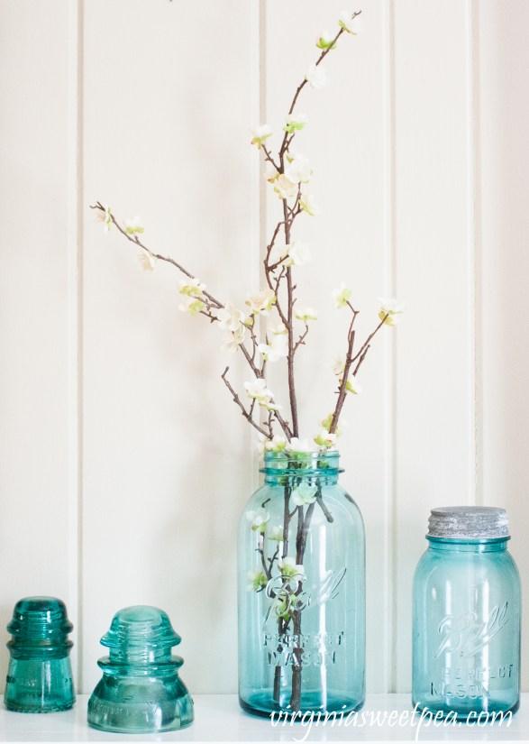 Vintage Blue Ball Jars and Insulators used on a Spring Mantel - #springmantel #springdecor #vintage #vintagedecor #balljars