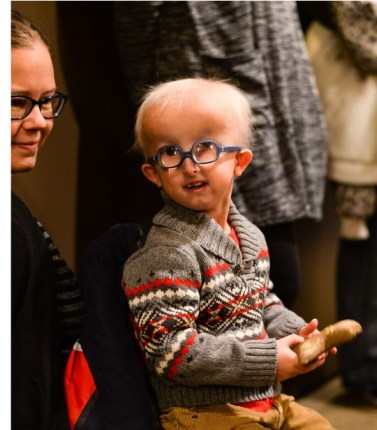 A little boy with glasses smiles into the camera