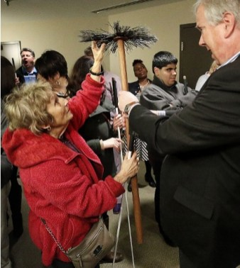An elderly woman reaches up to touch a prop
