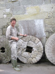 Michael Stoate at his mill in Shaftesbury next to some large millstones