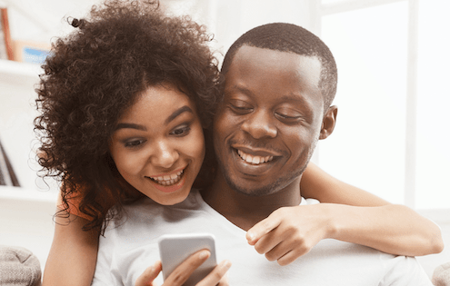 man and woman smiling over phone