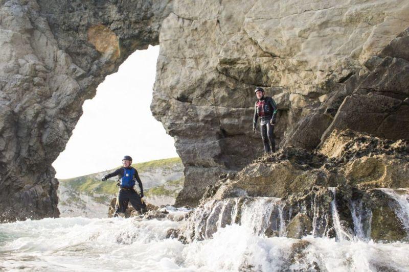 People coasteering at the Durdle Door limestone rock arch on the Dorset Jurassic coastline