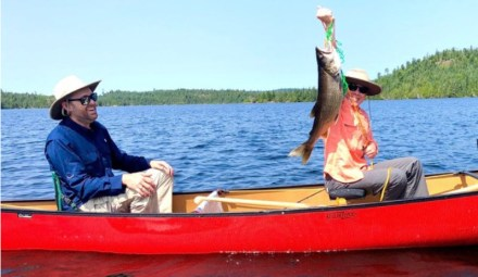Seagull Canoe Outfitters couple fishing from red canoe