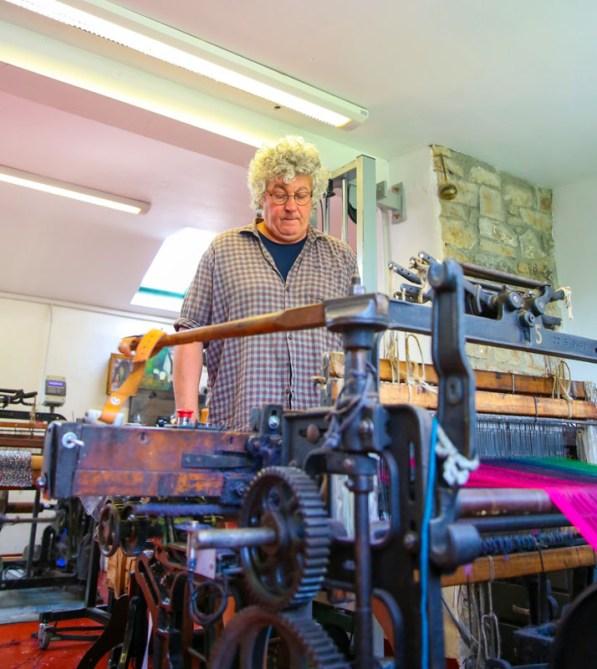 Eugene McKernan behind the Hattersley loom in McKernan Woollen Mills. The loom is weaving a scarf.