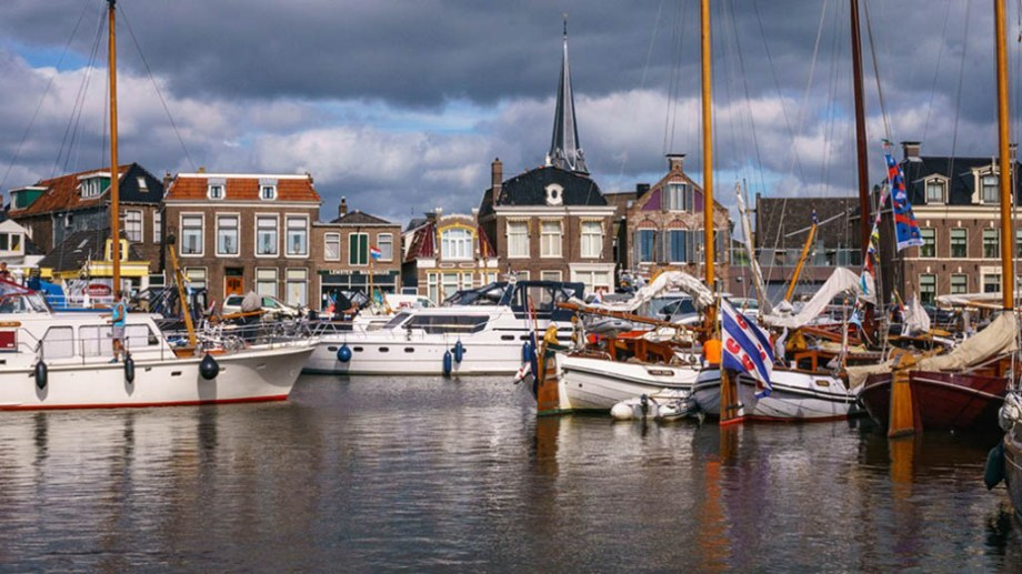 view on boats laying in the harbour of Lemmer, The Netherlands, with historic dutch buildings in the back