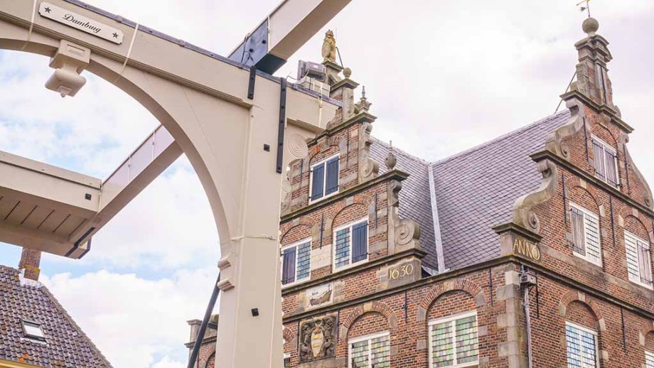 The top part of the town hall of De Rijp photographed with the white bridge in front of them
