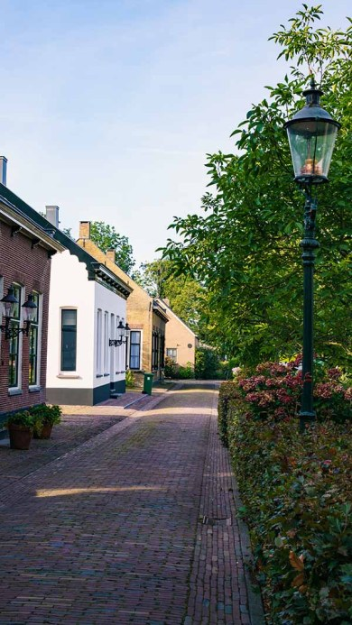 A beautiful cityscape with cobblestones and old historic houses in the beautiful Dutch village of Drimmelen, The Netherlands