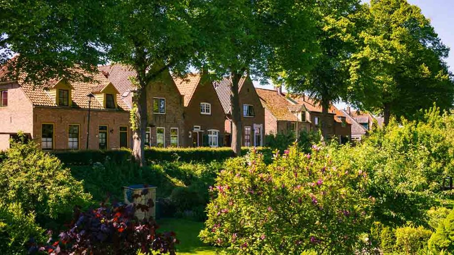 view from a green park on dutch historic brick houses during summer in Hattem, The Netherlands