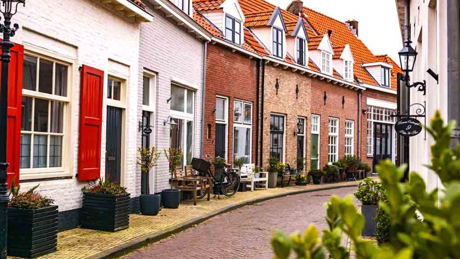 A curved cobblestoned street with old dutch brick houses in Harderwijk city The Netherlands