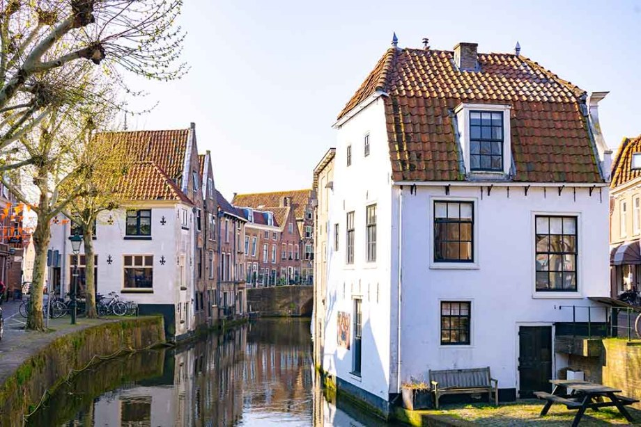 A photo of Oudewater city, with a curved canal in the middle that is surrounded by white and brown brick buildings with orange roofs