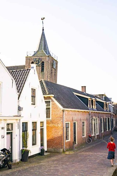 A photo of an old cobble stoned streets with historical buildings on the left side and a view on a 13th century church tower in Linschoten