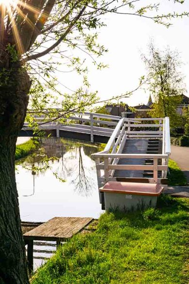 A pedestrian bridge with stairs crossing a small river