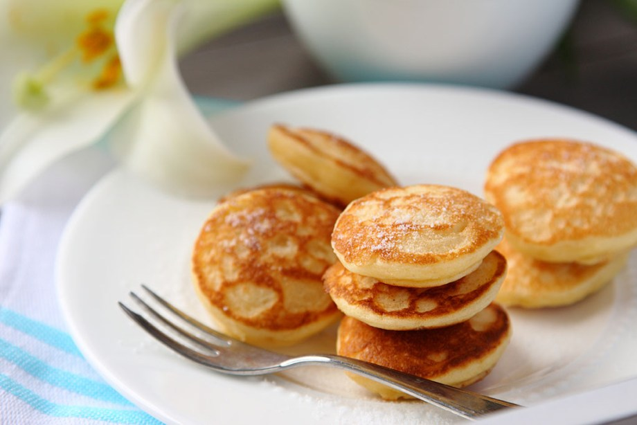 Dutch mini pancakes called poffertjes, sprinkled with powdered sugar