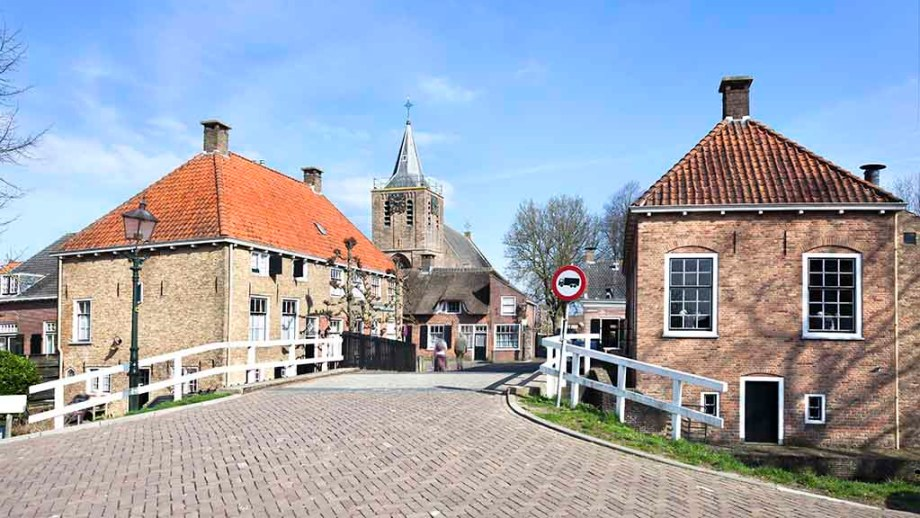 A photo of the village of Linschoten in The Netherlands: a bridge with historic buildings on the side and an 13th century church in the distance