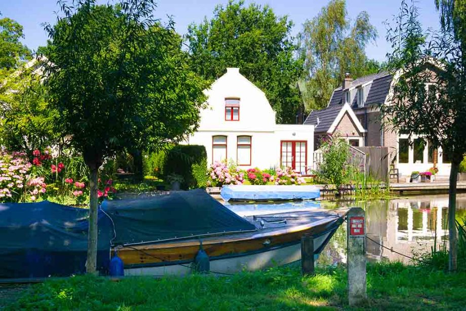 Dutch houses with a river and a boat in front of them in Abcoude, The Netherlands
