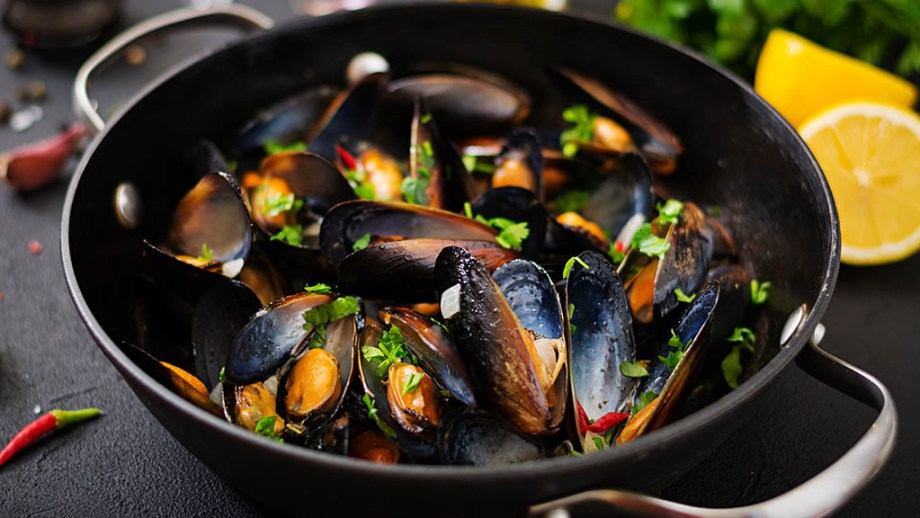 Dutch Mussels cooked in with herbs in a frying pan on a black background.