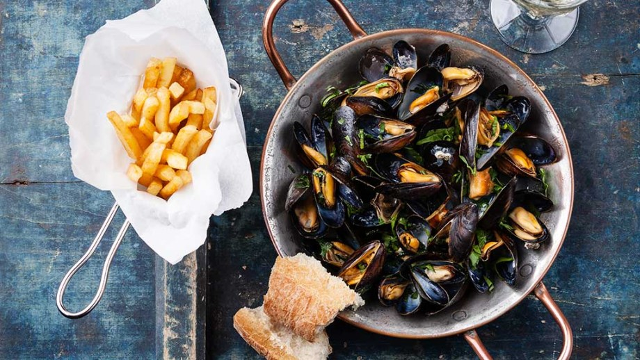 Dutch Mussels recipe made in copper cooking dish and french fries on blue background