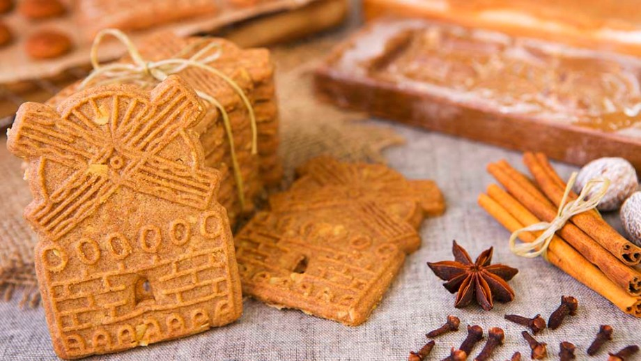 Traditional Dutch 'speculaas' (spiced shortcrust cookies). With authentic wooden cookie cutters especially made for these cookies in the background.