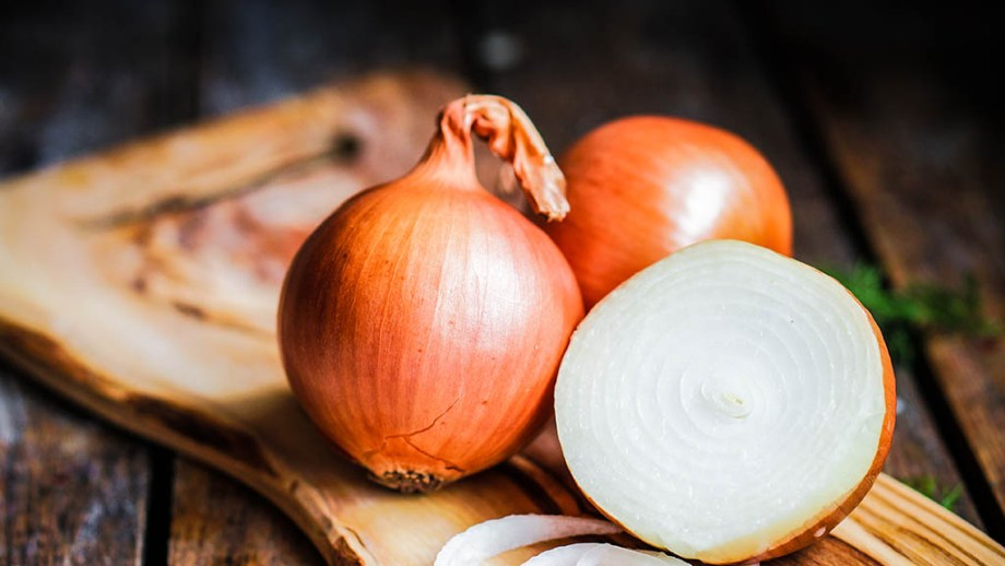 white onions on a wooden cutting board