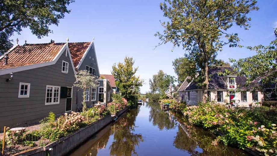 A river and old Dutch wooden coloured houses along them on a summer day in Broek op Waterland