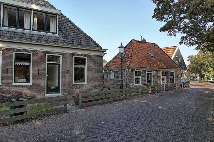 A view on old Dutch farms on a cobblestoned street in the village of Twisk