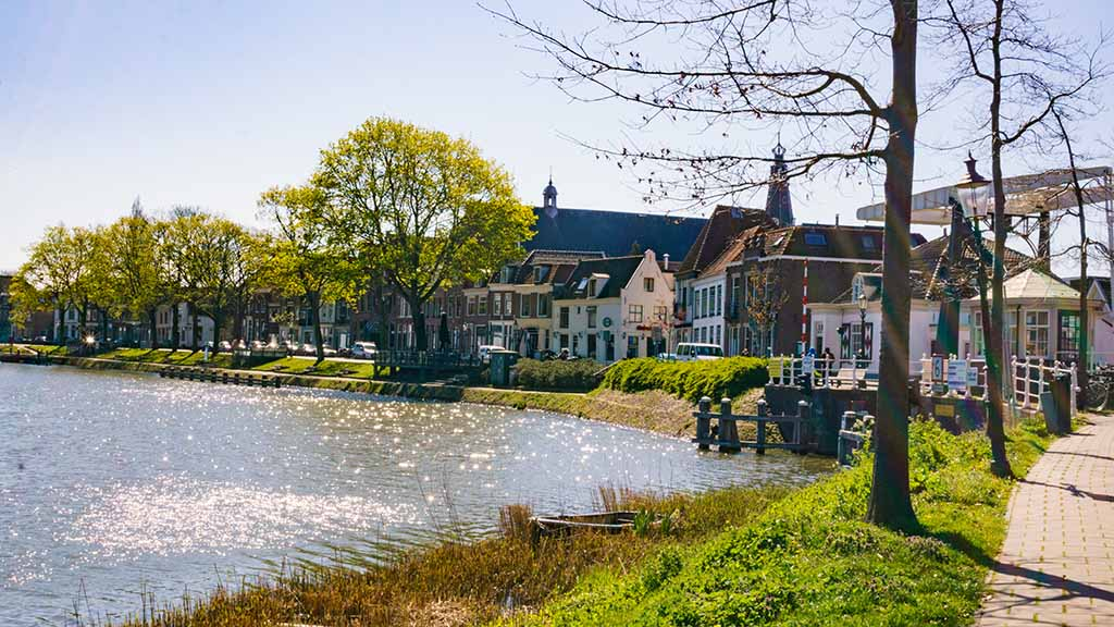 View on the river that flows through the city of Weesp and its beautiful canal houses in The Netherlands